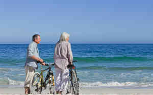 Elderly couple on beach with cycles